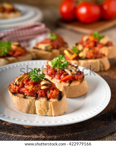 Delicious mussels bruschetta with tomato, parsley, olive oil, and garlic on grilled french bread.