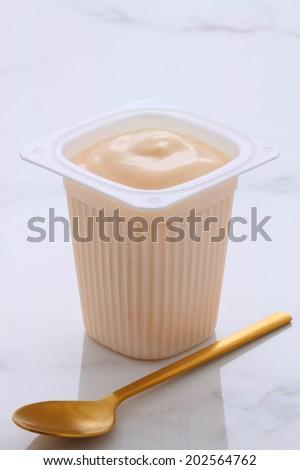Delicious, nutritious and healthy fresh plain yogurt cup. On vintage Italian carrara marble retro styling. - stock photo
