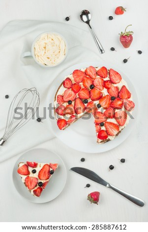 Delicious nutritious cake with fresh strawberries decorated with chokeberry, white cup with whipped cream, steel spoon, whisk, strawberry, napkin, plate, top view,  good morning - stock photo