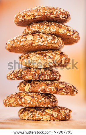 delicious oatmeal cookies with splash of sunflower seeds, sesame seeds on wooden table laid out in row