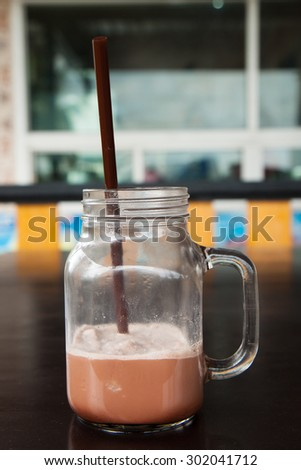 Delicious of chocolate frappe with straw in glass cup on black wood table. - stock photo