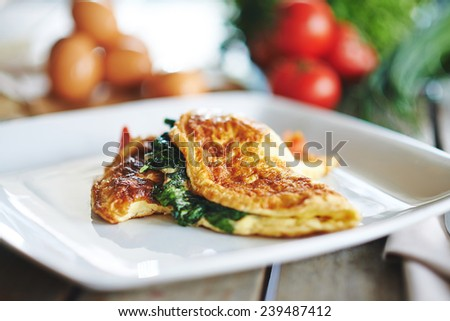 delicious omelet with spinach, cheese and tomatoes on the wooden table - stock photo