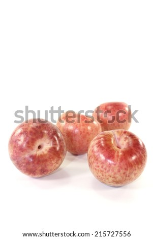 delicious orange-red pluots on a light background - stock photo