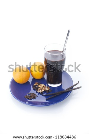 Delicious oranges, vanilla sticks and a glass of mulled wine on a blue plate, on isolated, white background