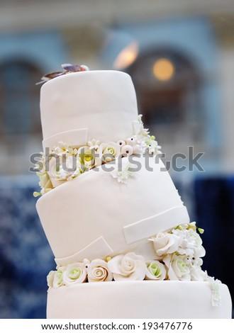 Delicious original wedding cake decorated with cream roses - stock photo