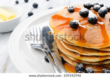 Delicious pancakes stack with fresh blueberries and flowing dripping maple syrup - stock photo