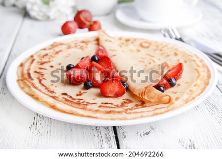 Delicious pancakes with berries on table close-up - stock photo