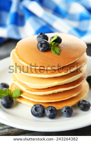 Delicious pancakes with blueberries on blue wooden background - stock photo