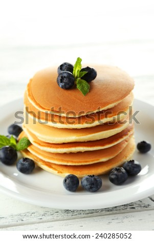 Delicious pancakes with blueberries on white wooden background - stock photo