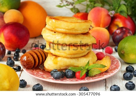 Delicious pancakes with honey, fruits and berries - stock photo