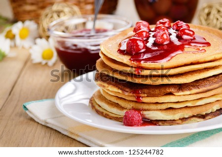 Delicious pancakes with raspberries on the wooden kitchen table