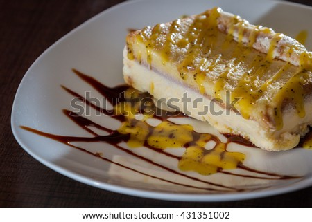 delicious passion fruit ice cream cheese cake served on a white plate with a chocolate drizzle as a garnish