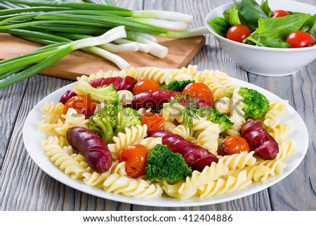 delicious pasta salad with broccoli, grilled sausages and tomatoes on a white dish with fresh tomato and sorrel spring onions on a cutting board on the background, close up - stock photo