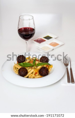Delicious pasta served with sauces and red wine - stock photo