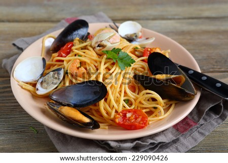Delicious pasta with squid, mussels and tomato, on the boards - stock photo