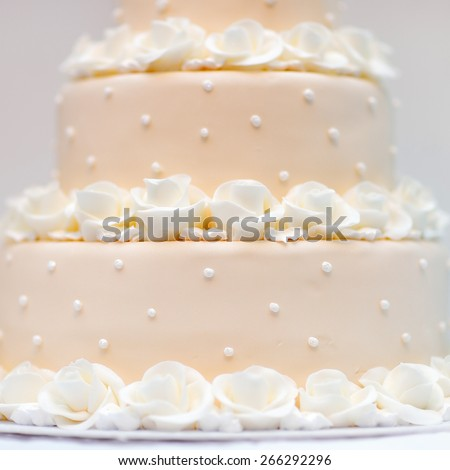 Delicious peach and white wedding cake decorated with cream roses  - stock photo