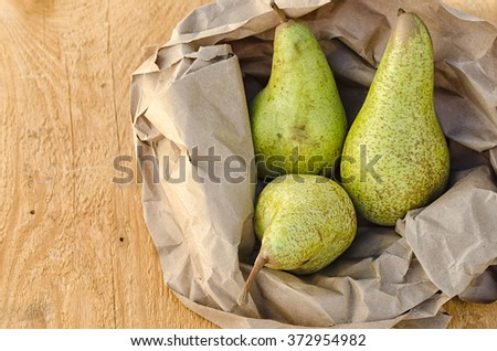 Delicious pears in brown paper on wooden table. - stock photo