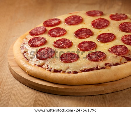 Delicious Pepperoni Pizza on board - stock photo