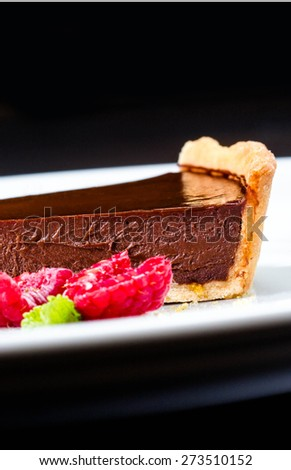 Delicious Piece of Chocolate pie. Chocolate cheesecake with raspberries. Dark chocolate cake with chocolate sauce macro - stock photo