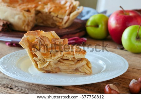 delicious piece of homemade apple pie closeup on a white plate on a wooden table