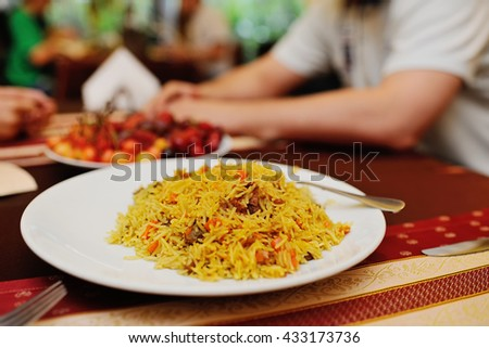delicious pilaf with meat on the table against the background of the restaurant