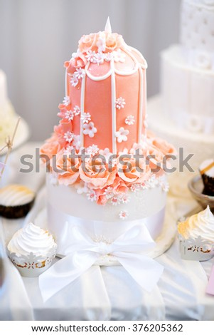 Delicious pink wedding cake decorated with sugar flowers - stock photo