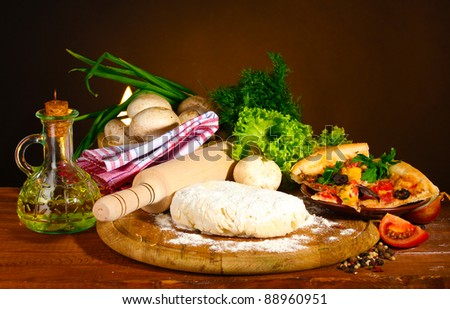 delicious pizza dough, spices and vegetables on wooden table on brown background - stock photo