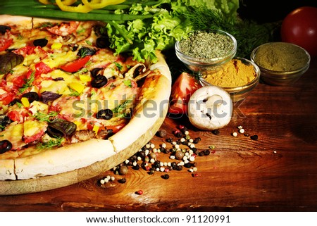 delicious pizza, vegetables and spices on wooden table - stock photo