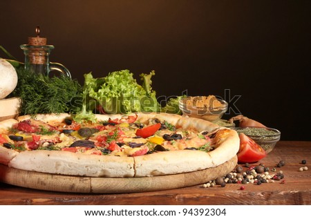 delicious pizza, vegetables and spices on wooden table on brown background - stock photo