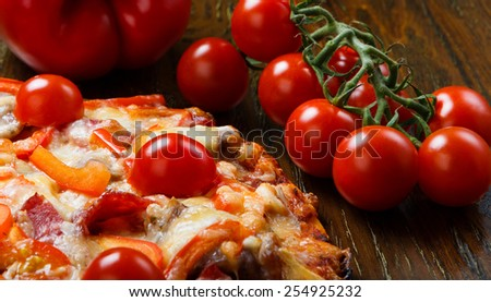 Delicious pizza with bacon, salami, cherry tomatoes and peppers - stock photo