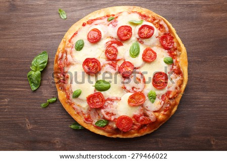 Delicious pizza with cheese and cherry tomatoes on wooden table, top view - stock photo