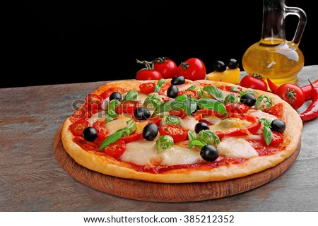 Delicious pizza with cheese and vegetables on black background