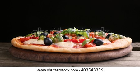 Delicious pizza with cheese and vegetables on black background - stock photo