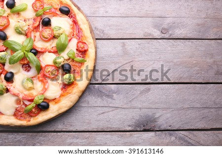 Delicious pizza with cheese and vegetables on wooden background - stock photo