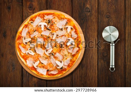 Delicious pizza with mushrooms and smoked chicken meat - thin pastry crust isolated at wooden background  with stainless steel cutter, above view - stock photo
