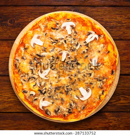 Delicious pizza with mushrooms - thin pastry crust isolated at wooden background, above view - stock photo