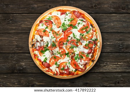 Delicious pizza with mushrooms, tomatoes and chicken ham - thin pastry crust at wooden round desk and rustic wood background. Italian food. Top view - stock photo