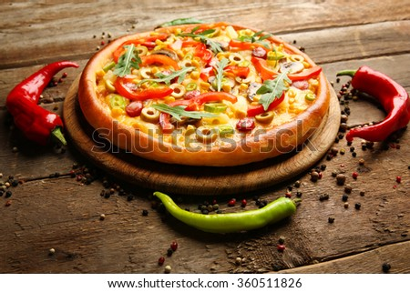 Delicious pizza with pepper on wooden background