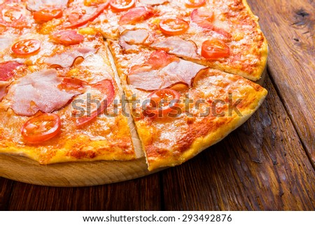 Delicious pizza with peppers, bacon and cherry tomatoes - thin pastry crust isolated at wooden background on wooden desk - stock photo