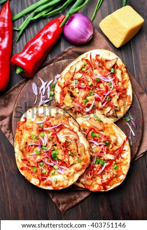 Delicious pizza with red pepper on wooden table, top view - stock photo