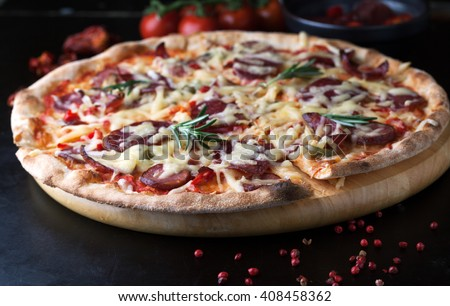 Delicious pizza with salami, tomatoes and hot peppers on wooden background - stock photo