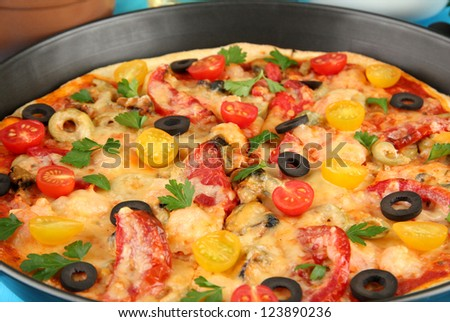Delicious pizza with seafood in the frying pan close-up