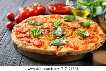 Delicious pizza with tomatoes and fresh basil on kitchen table
