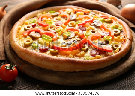 Delicious pizza with vegetables on wooden table - stock photo
