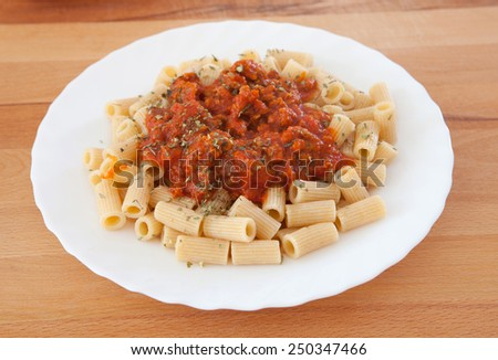 Delicious plate of macaroni with tomato close up - stock photo
