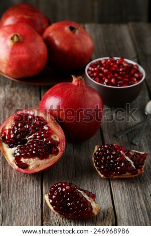 Delicious pomegranate fruit on grey wooden background - stock photo