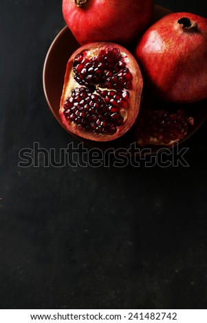Delicious pomegranate fruit on plate on black background - stock photo
