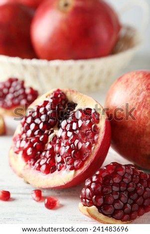 Delicious pomegranate fruit on white wooden background - stock photo