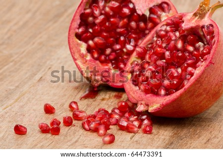 Delicious pomegranate with seeds on wooden table - stock photo