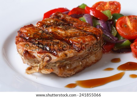 Delicious pork steak with vegetables and sauce on a plate close-up, horizontal  - stock photo